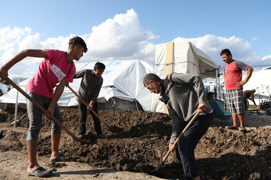 Men dig next to tents in the Kara Tepe camp for refugees and migrants on the island of Lesbos