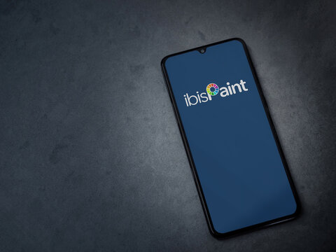 Lod, Israel - July 8, 2020: Ibis Paint X app launch screen with logo on the display of a black mobile smartphone on a dark marble stone background. Top view flat lay with copy space.