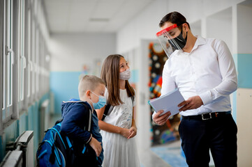 Elementary school students and male teacher wearing protective face masks at school