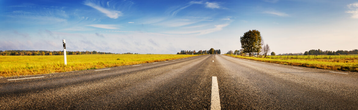 Asphalt road panorama in countryside on sunny autumn day