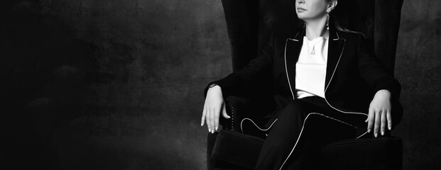 Black and white cropped photo of a woman in a black pantsuit sitting in a high chair in a...