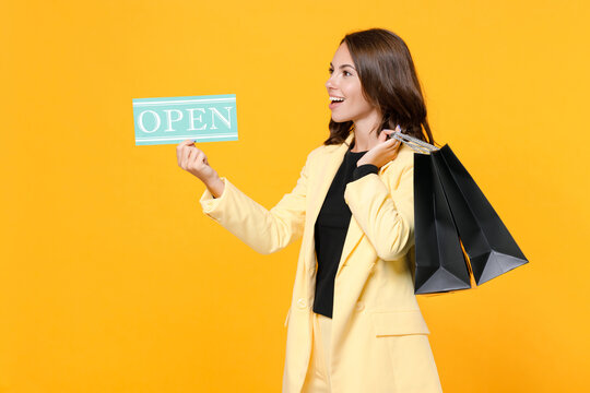 Smiling young woman 20s in basic light suit jacket hold package bags with purchases after shopping sign with OPEN title looking aside isolated on yellow background, studio portrait. Black friday sale.