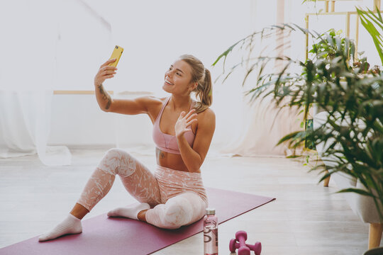 Smiling young strong sporty fitness woman wearing pink tracksuit doing yoga exercises sitting making selfie shot on mobile phone waving greeting with hand stretching on mat floor at home indoor.