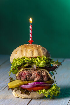single cheeseburger with a burning candle