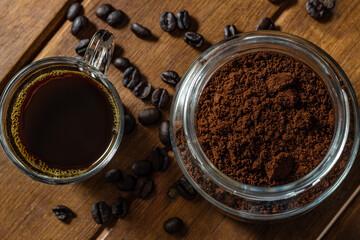 Detalhe de xícara de café com vidro cheio de pó de café e grãos espalhados sobre a mesa de madeira.