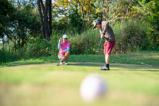 Couple golf player putting golf ball on the green golf.  Asia man and woman putting golf ball on tee with club in golf course on evening on time for healthy sport.