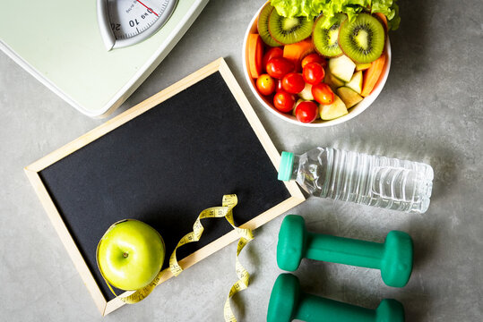 Workout and diet Health Plan. Sport exercise equipment workout and gym with fresh salad and green apple for fitness style.