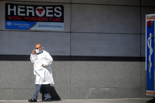 A doctor speaks on his phone outside the Emergency entrance to Maimonides Medical Center in the Borough Park neighborhood of Brooklyn, New York