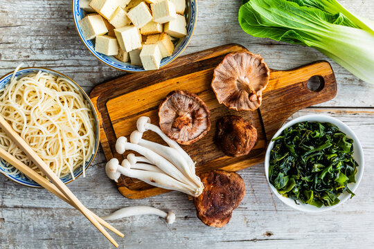 Fresh mushrooms and ingredients for miso soup on a wooden background.