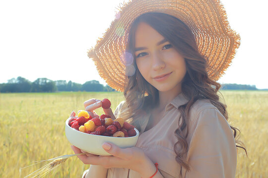 girl raspberries eating a picnic field sun / adult young model eating raspberries in a sunny summer field, enjoying happiness romance