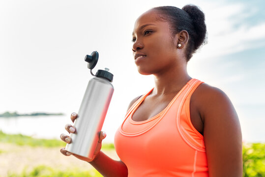 fitness, sport and healthy lifestyle concept - young african american woman drinking water from bottle outdoors