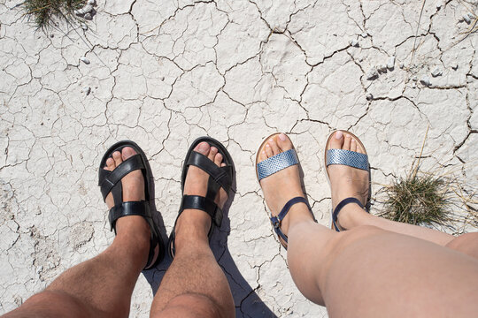 Male and female feet in open shoes, sandals. View from above. They stand on dry ground with cracks, a little dried grass. Heat, heat.
