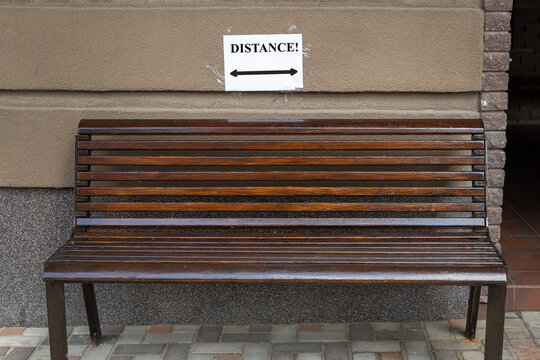 Paper sheet with message text appeal to keep social distance attached over empty wooden bench near office or residential building at city street. Covid-19 coronavirus disease outbreak pandemic