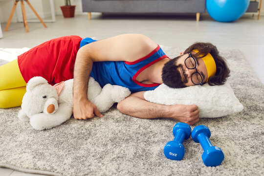 Lazy athlete sleeping peacefully on the floor, hugging a teddy bear, with dumbbells beside