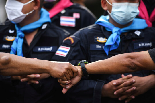Pro-democracy protesters hold hands as they gather demanding the government to resign and to release detained leaders in Bangkok