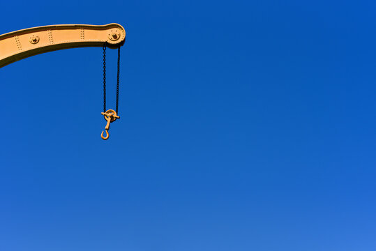 old dock crane on chains with hook on clear blue sky background
