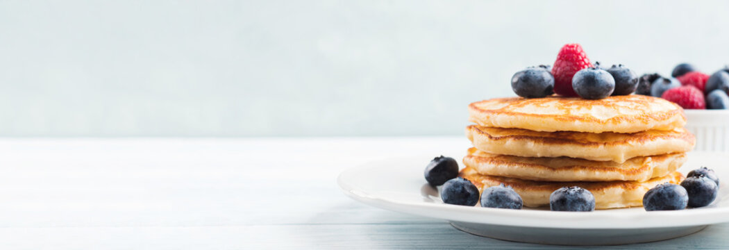 Stack of pancakes with fresh blueberries served in a dish with maple syrup. Delicious breakfast