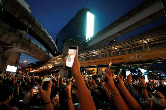 Pro-democracy protesters hold up their mobile phones during anti-government protests in Bangkok