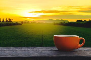 Hot coffee cup Ceramic brown glass placed on an outdoor old wood table. The background is a landscape of nature with mountains and rice field