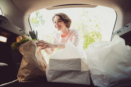 Photo of girl shopper put shopping bags in car trunk cabin ready ride drive home cook family husband meal in town center outside