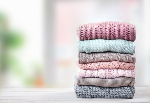 Stack of knitted textured clothing on table.Colorful winter clothes,warm apparel.Heap of knitwear.