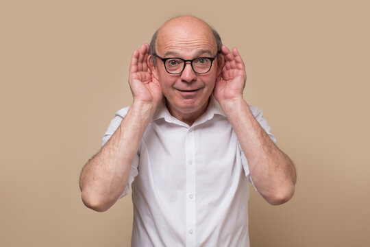 Senior bald male adult in glasses listening carefully, spying, being curious. Studio shot
