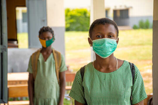two school kids wearing face masks and physically distancing themselves