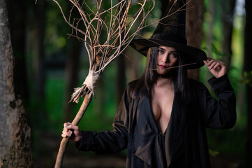 Portrait of beautiful asian sexy woman wear black witch costume with broom,Halloween festival...