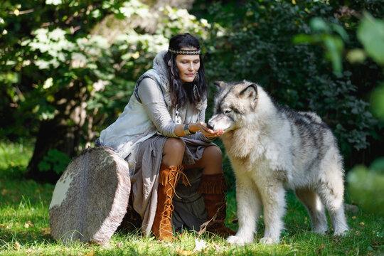 Shaman woman feeding the Alaskan Malamute dog in the forest