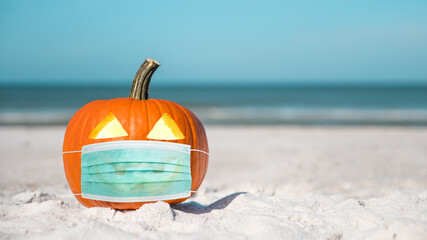 Halloween party on the beach. Carved Pumpkin Jack-o'-lantern with Medical face Mask. Jack o lantern for Happy Halloween. Autumn season. On background ocean. Autumn in Florida. Fall season. Copy space.