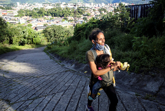 Yaidis Colmenares walks towards the border between Venezuela and Colombia with her one-year-old baby strapped to her chest during the coronavirus disease (COVID-19) outbreak in San Cristobal, Venezuela