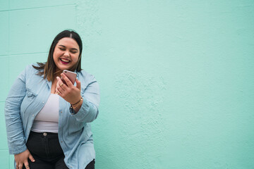 Young plus size woman using her mobile phone.