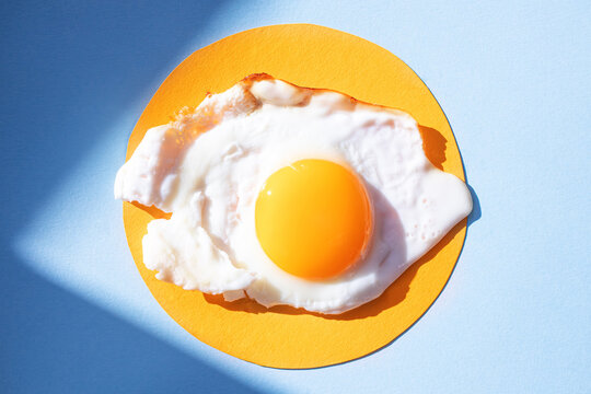 Fried eggs on a light orange and blue background, pattern. Breakfast concept, fried food. Minimalism, top view.