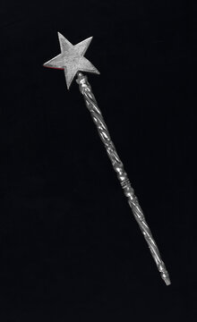 silver magic wand with star isolated on black background
