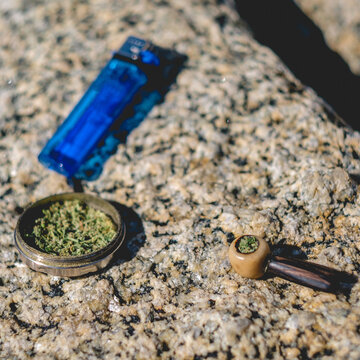 Little wooden pipe with marijuana, grinder and blue lighter over a rock of the beach in a sunny day