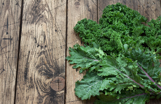 Fresh variety kale leaves on the wooden background. healthy food. superfood. flat lay. space. rustic style.