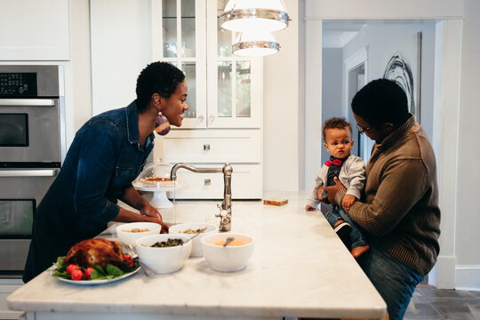 Young Black family prepares food in kitchen for holiday gathering