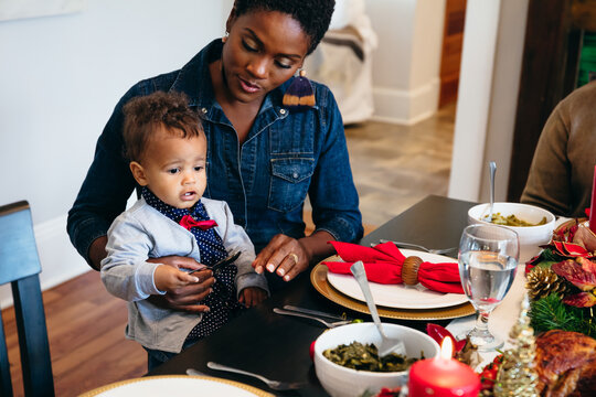 Black mother and child eating dinner for the holidays