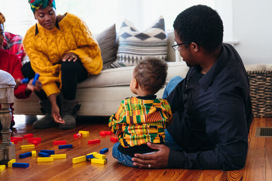 Black family playing with blocks in living room