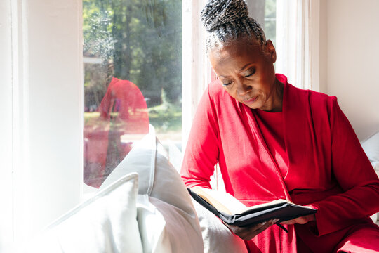Senior Black woman with grey hair sitting by window and reading book