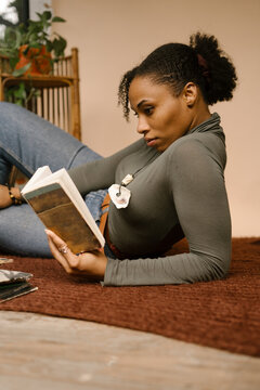 Black woman reading book and enjoying self care at home