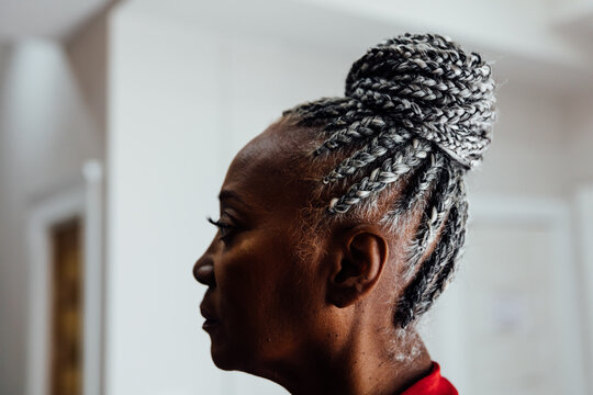 Profile of Senior Black woman with grey hair and braids