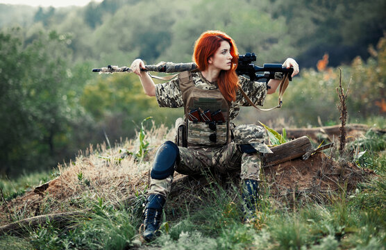 Sniper girl in a green field. Military snipers. The sniper smokes. Red-haired girl in camouflage. Fighting