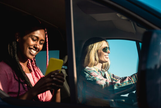 Happy multiracial friends driving on road trip while using gps mobile phone app - Lifestyle camper tech concept - Focus on girl on right