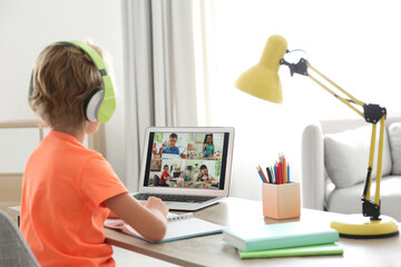 Little boy studying with classmates via video conference at home. Distance learning during COVID-19...