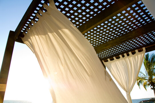 Beach cabanas with lounge chairs and curtains.