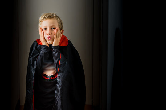 Young boy in vampire costume on halloween scared in a dark hallway.