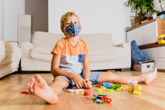 Blond boy plays at home with toys and wears a mask on his face.