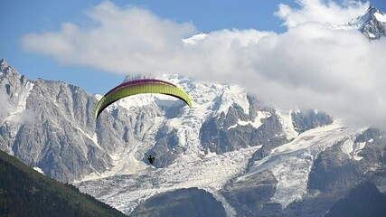 Wall Mural - Summer Paragliding in French Alps. Paraglider and Mont Blanc Massif in Background. Slow Motion Footage