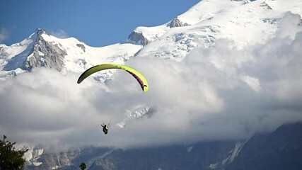 Wall Mural - Professional Paraglider Extreme Sportsman and Mont Blanc Massif in Background. French Alps. Slow Motion Movement.